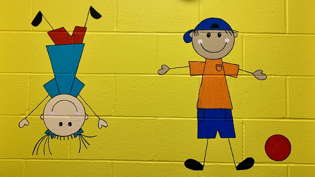 Painting on the wall of two kids. One kicking a ball and the other doing a hand stand.